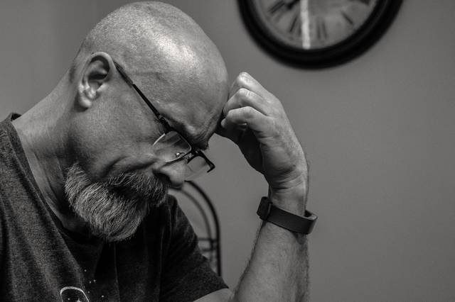 grayscale-photo-of-man-thinking-in-front-of-analog-wall-1194196.jpg