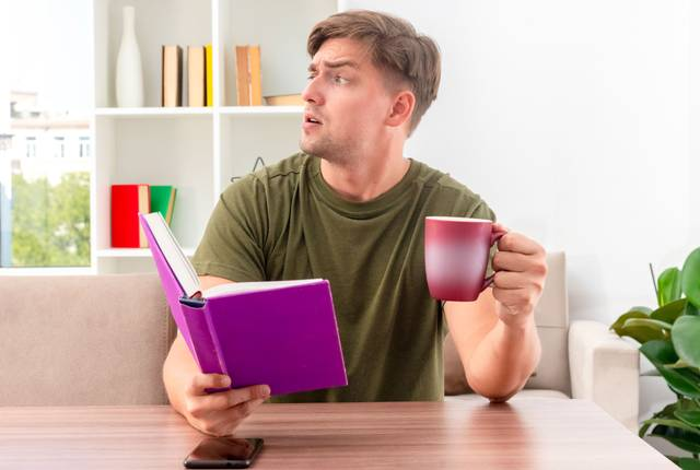 annoyed-young-blonde-handsome-man-sits-at-table-with-phone-holding-book-and-cup-looking-at-side-inside-the-living-room.jpg